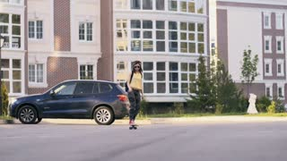 Young Beautiful Woman In Leggings Longboarding On The Street