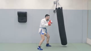 Young Fighter Trains With Punching Bag In The Gym. Slow-Mo