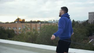 Young Male Athlete Jumping By The Skipping Rope On The Roof. Cinematic