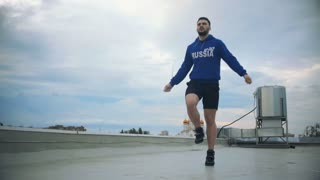 Young Male Athlete Jumping By The Skipping Rope On The Roof. Slow-Mo. Cinematic