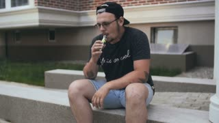 Young Man Sitting Near House On The Street And Smoke E-Cigarette. Vape. Slow-Mo
