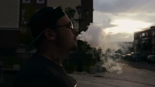 Young Man Smoke E-Cigarette At Sunset. Vape. Slow-Mo.