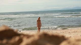 Young pretty woman in bikini on the beach. Sunny day in Bali. Indian Ocean