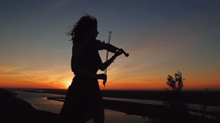 Young woman on the mountain playing the violin on river background at sunset