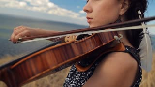 Young woman on the mountain playing the violin on sea background. Steadicam Shot