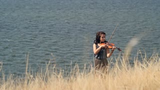 Young woman on the mountain playing the violin on sea background