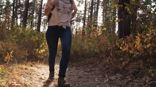 Young woman with a backpack walking in the autumn forest. Steadicam shot