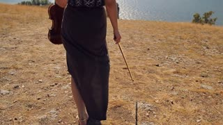 Young woman with a violin walking on the mountain to the sea. Steadicam Shot. Slow motion