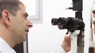 An optometrist uses a slit lamp machine