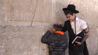 Editorial only clip of kid bless his younger brother as the pray at the Kotel