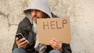 Homeless with help sign using smartphone