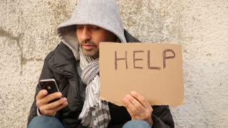 Homless with iPhone, Young man sitting on the street seeking for financial help