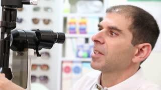 Optometrist using slit lamp machine