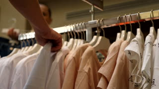 Female customer in closing shop choosing clothes in different colors