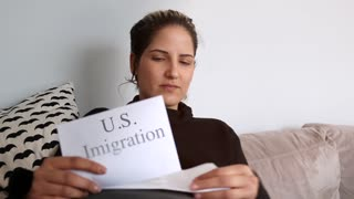 Woman Sitting On Couch Reading Usa Immigration Papers