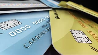 A few color credit cards rotate on a glossy black background. Closeup shot with depth of fields. Shopping concept. Seamless loop.