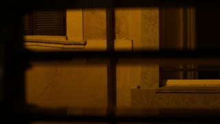 Closeup view through Window shutters on a lane. Italy.