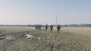 Soldiers with weapons run on camera.