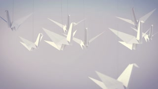 An impressive 3d rendering of soaring white paper cranes in the grey background. They look tender, defenseless, and unintentional in this highly pragmatic world.