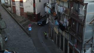 Cyclist riding through narrow streets of Porto, Portugal