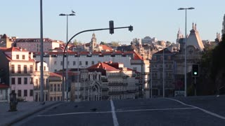 Downtown Porto, Portgal early morning buildings empty car driving up road
