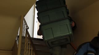Man carrying heavy bins down stairs
