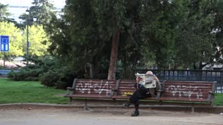 Man covered face reading newspaper on bench