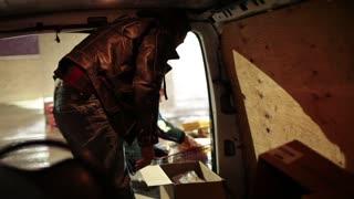 Man loading groceries into van