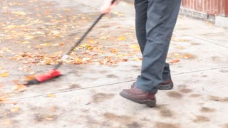 Man sweeping leaves away outside