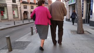 Old couple walking arm in arm