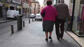 Old couple walking together arm in arm