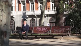 Old man deep in thought sitting on bench