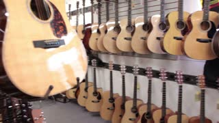 Pan of acoustic guitars in store wide shot