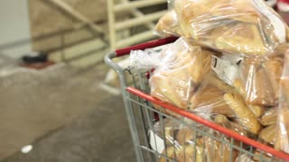 Pan of bags of bread in shopping cart being loaded