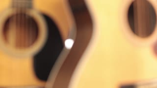 Rack focus close up CU upright acoustic guitars