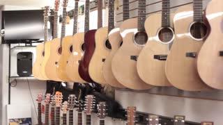Tilt pan down row of acoustic guitars