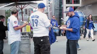 Toronto blue jay sports fans eating hotdog from stand with band from behind