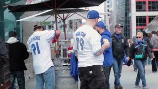 Toronto blue jay sports fans eating hotdog from stand