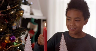 A happy boy lights a holiday candle with a smile. Christmas tree in background.