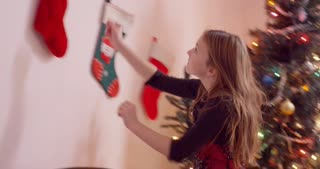 Excited young girl runs up to take Christmas stocking off the wall and examines the content.