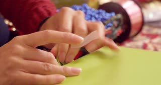 Female hands finishes wrapping a present with tape.