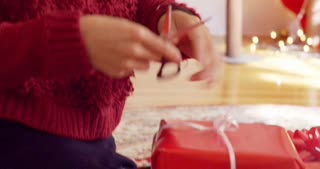 Female ribbon stripping on wrapped Christmas presents.