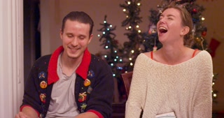 Friends having a fun time at a holiday party, laughing and smiling. Slow motion.