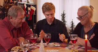 Grandpa jeering and mocking his Grandson over a family card game at Christmas
