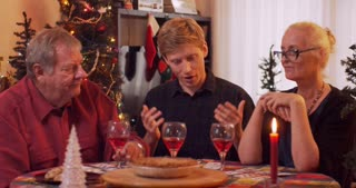 Grandson and Grandparents toast and cheers drinks at family holiday dinner - slow motion