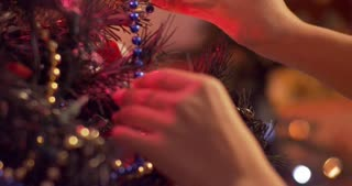 Woman hands decorating a Christmas tree and adding final touches - slow motion