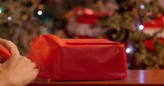 Woman wrapping and taping a present in front of Christmas decorations - slow motion
