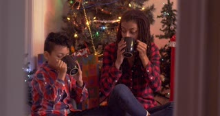 Mother and son drinking hot chocolate in front of a Christmas tree and exchanging a gift - mixed - slow motion
