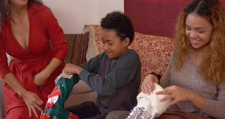 Mother hands children Christmas stockings. They give mom a hug after going through it.