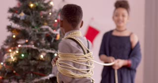 Silly boy wraps around in Christmas beads, controlled by his sister.